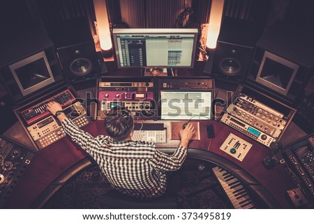 Sound engineer working at mixing panel in the boutique recording studio. - stock photo