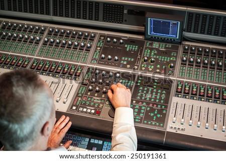Sound engineer working in studio - stock photo