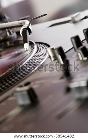Sound mixer and turntable vinyl record player playing analog disc with music. Sound enthusiast or professional DJ audio equipment. Sound recording studio,focus on turntables needle