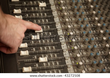 sound producer moving one fad of dusty sound mixer - stock photo