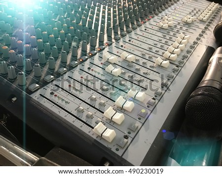 Sound system mixing audio equipment board on stage with soft light filter