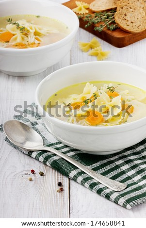 Soup chicken in a bowl with spoon on a white wooden table