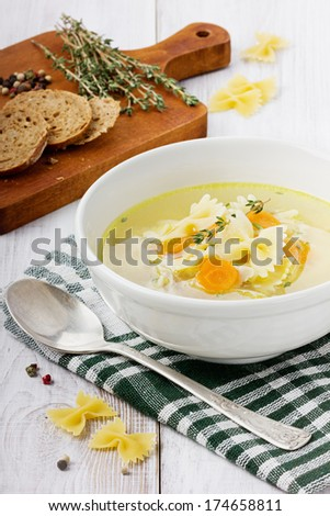 Soup chicken in a white bowl with spoon on a white wooden table - stock photo