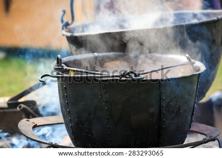 Soup cooking in medieval pot - stock photo