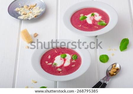Soup from beet with light creame, nuts and basil sprinkled, organic beet