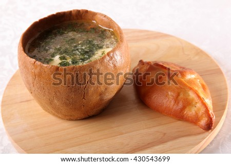 soup in a pot of dough and pie on wood - stock photo