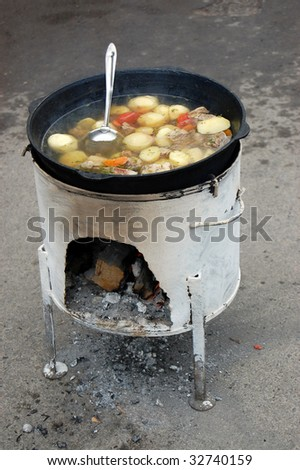 Soup in cauldron on street - stock photo