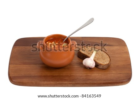 Soup in clay pot with bread and garlic on wooden kitchen board. Isolated on white background
