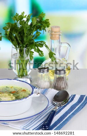 Soup in plate on napkin on table on window background