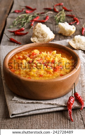 Soup of red lentils and vegetables in a wooden plate - stock photo