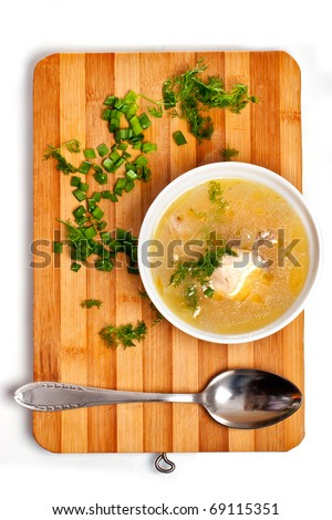 Soup plate on kitchen chopping board - stock photo