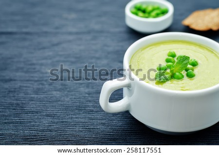 soup puree of green peas on a black background. tinting. selective focus - stock photo