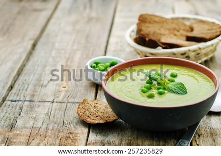 soup puree of green peas on a dark wood background. tinting. selective focus - stock photo