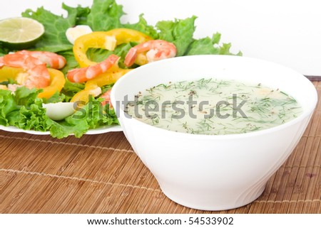 Soup with a salad on a wooden tablecloth - stock photo