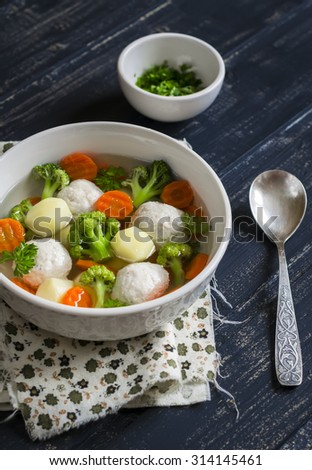 soup with chicken meat balls, potatoes, broccoli and carrots in a white bowl, a Healthy and tasty lunch