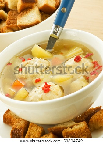 Soup with chicken meatballs and croutons. Shallow dof. - stock photo