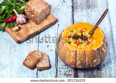 Soup with lentil decorated in the carved pumpkin with bread pieces on the blue wooden background at autumn holidays - stock photo