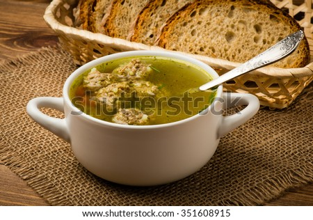 Soup with meatballs in a white bowl on the wooden background. - stock photo