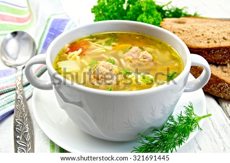 Soup with meatballs, noodles and vegetables in a white bowl, bread, napkin and spoon on the background light wooden boards