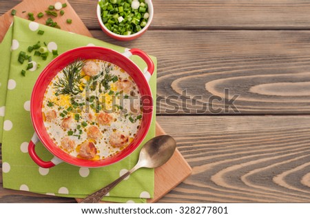 Soup with meatballs on wooden background - stock photo