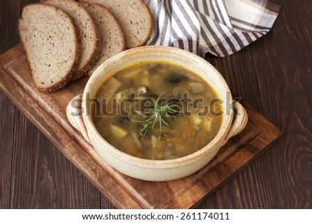 Soup with mushroom on wooden table - stock photo