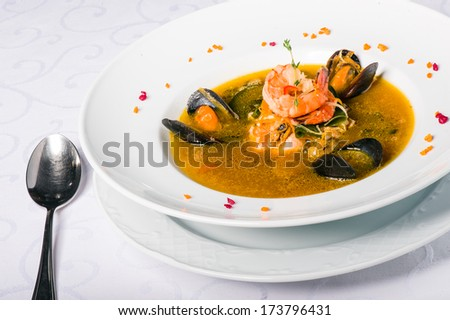 Soup with mussels, tiger shrimp, walleye, squid, salmon and vegetables - stock photo