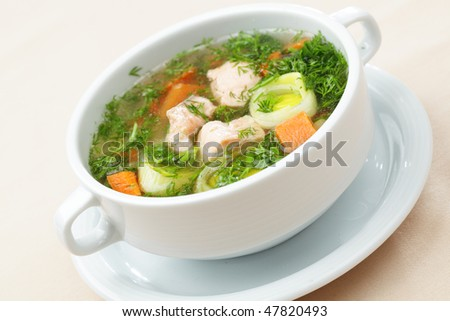 Soup with salmon and vegetables in a white bowl