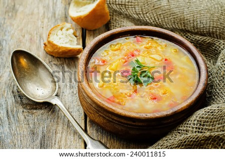 soup with salmon, potatoes and millet on a dark woody background. tinting. selective focus - stock photo