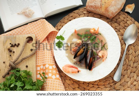 soup with seafood on a background of bread and books - stock photo