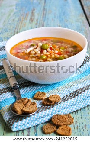 Soup with small pasta, vegetables and pieces of meat in a ceramic bowl on a wooden surface