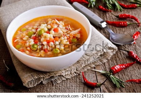Soup with small pasta, vegetables and pieces of meat in a ceramic bowl on a wooden surface - stock photo