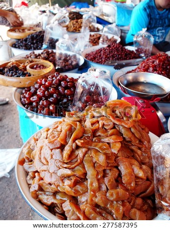 sour and sweet pickled tamarind for sale with other colorful local tropical conserved fruits on a street market BANGKOK, THAILAND - stock photo