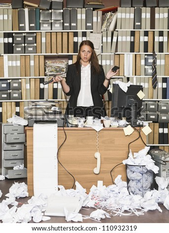 Sour businesswoman in a messy office - stock photo