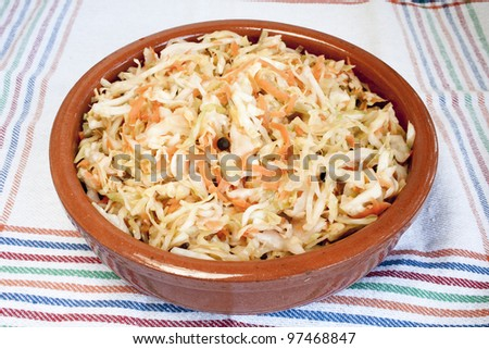 Sour cabbage in ceramic bowl with cabbage and carrot - stock photo