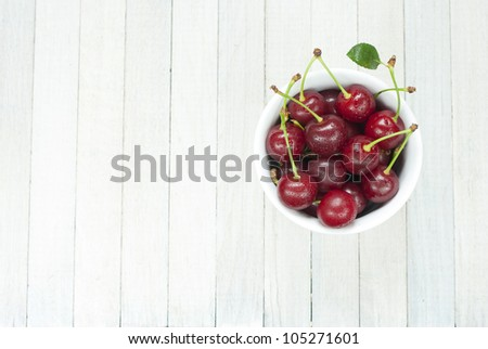 sour cherries in china dish on white wooden table, directly above - stock photo