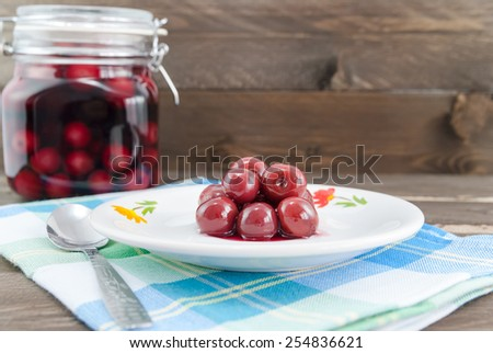 Sour cherries on white plate and in the background the jar with sour cherry compote - stock photo