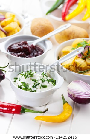 Sour cream and chutney with baked potatoes - stock photo