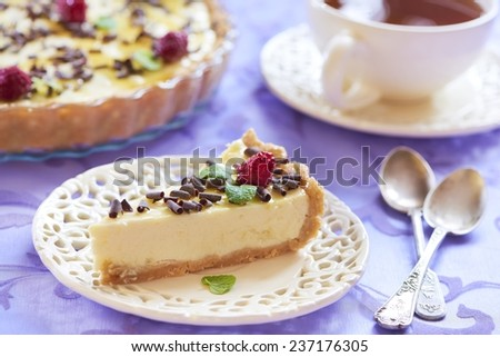 Sour cream cheesecake with chocolate chips, raspberries and mint - stock photo