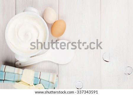 Sour cream in a bowl and eggs on wooden table. Top view with copy space - stock photo