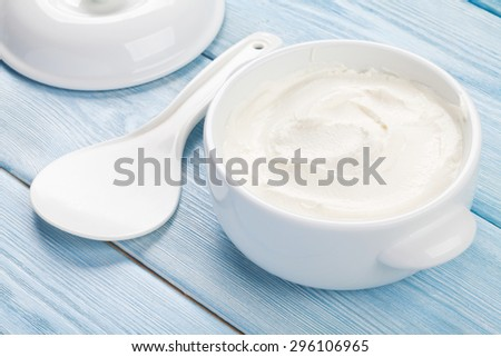 Sour cream in a bowl on wooden table