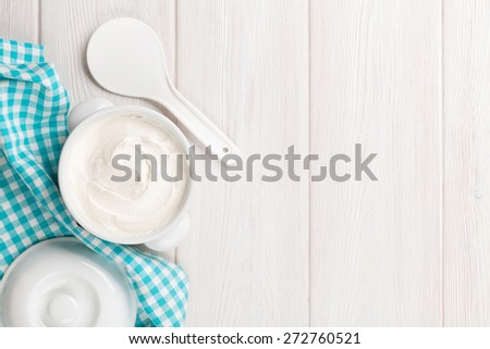 Sour cream in a bowl on wooden table. Top view with copy space - stock photo