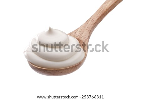 Sour cream in wooden spoon isolated - stock photo