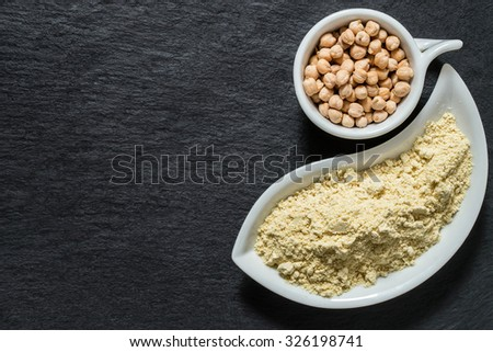 Source of vitamins A, E, groups B, manganese, calcium, selenium - chickpeas and chickpea gluten-free flour on a slate surface with copy space - stock photo