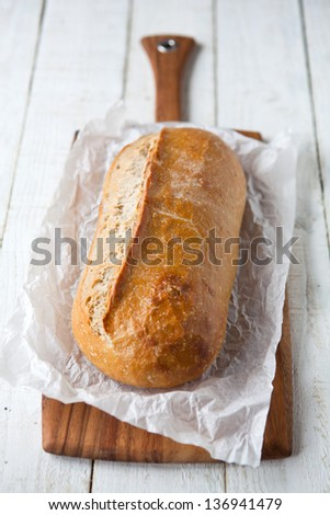 Sourdough bread loaf on a chopping board - shallow dof - stock photo