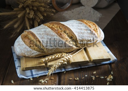Sourdough bread with wheat ears and flour on the bakery table - stock photo