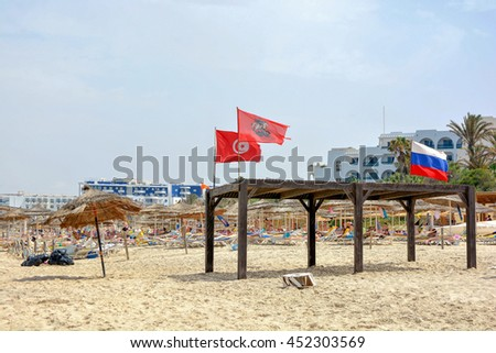 SOUSSE,TUNISIA - JULY 2,2016:Gazebo with flags on the beach of the Mediterranean sea