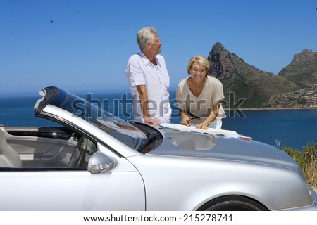 South Africa, Cape Town, senior couple standing by car with map, smiling, sea in background - stock photo
