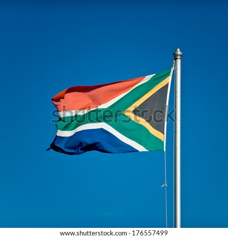 South African flag blowing in the wind on a flagpole. - stock photo