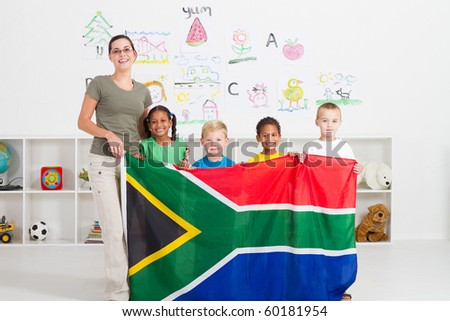 south african kindergarten teahcer and students with south africa flag - stock photo