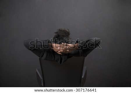 South African or African American black woman teacher or student sitting on a chair with her arms behind her head against a chalk blackboard background inside - stock photo